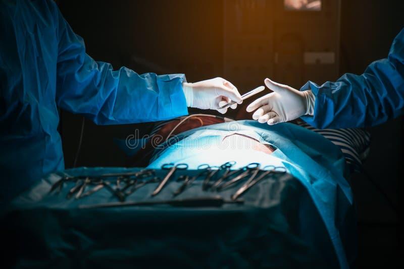 Plan rapproché des mains enfilées de gants tenant l'outil chirurgical Opération d'équipe de chirurgie photographie stock libre de droits