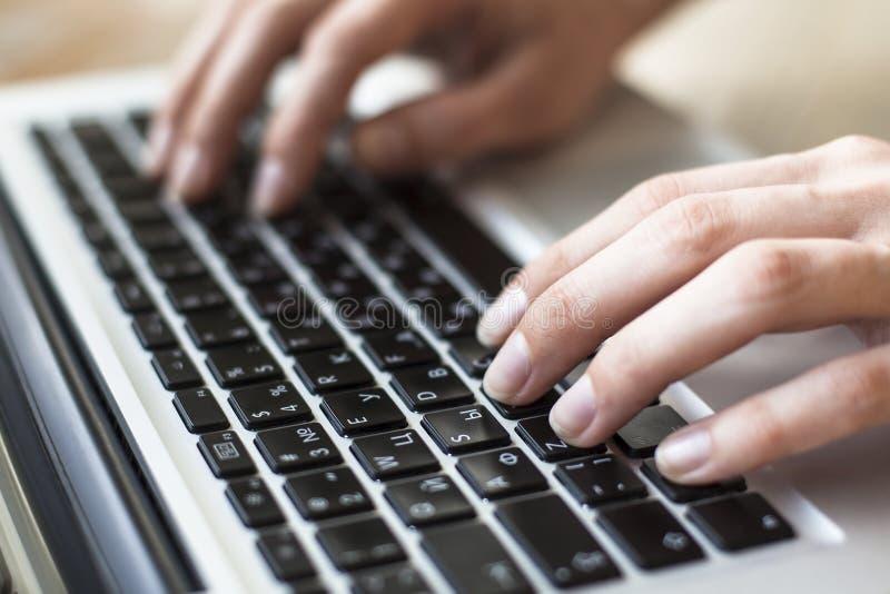 Plan rapproché des mains femelles dactylographiant le texte sur le clavier de l'ordinateur portable ou de l'ordinateur Gestionnai image libre de droits