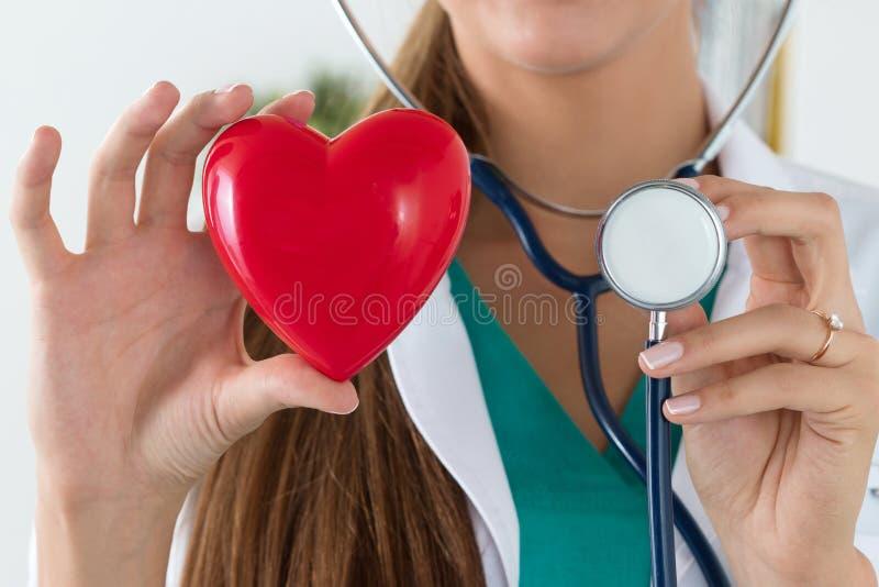 Plan rapproché des mains femelles de docteur tenant le coeur et le stethosco lus image libre de droits
