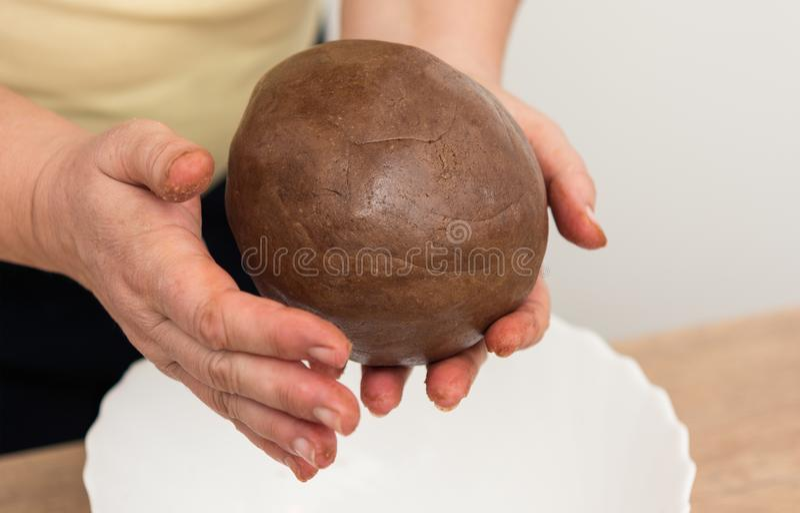 Plan rapproché des mains femelles en malaxant une boule de pâte brune photographie stock