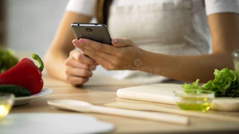 Plan rapproché des mains femelles faisant défiler sur le smartphone, femme choisissant la recette de salade image stock