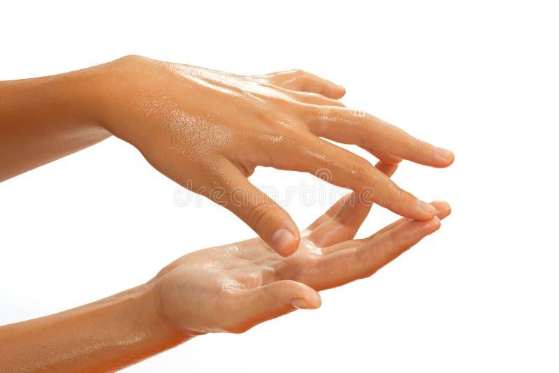 Plan rapproché des mains femelles tout en appliquant l'huile images libres de droits