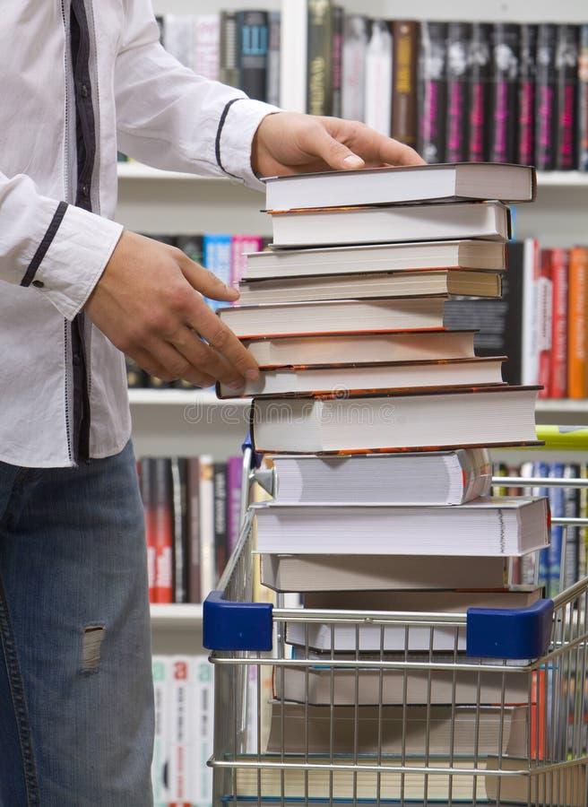 Plan rapproché des mains mettant des livres dans le panier photo libre de droits