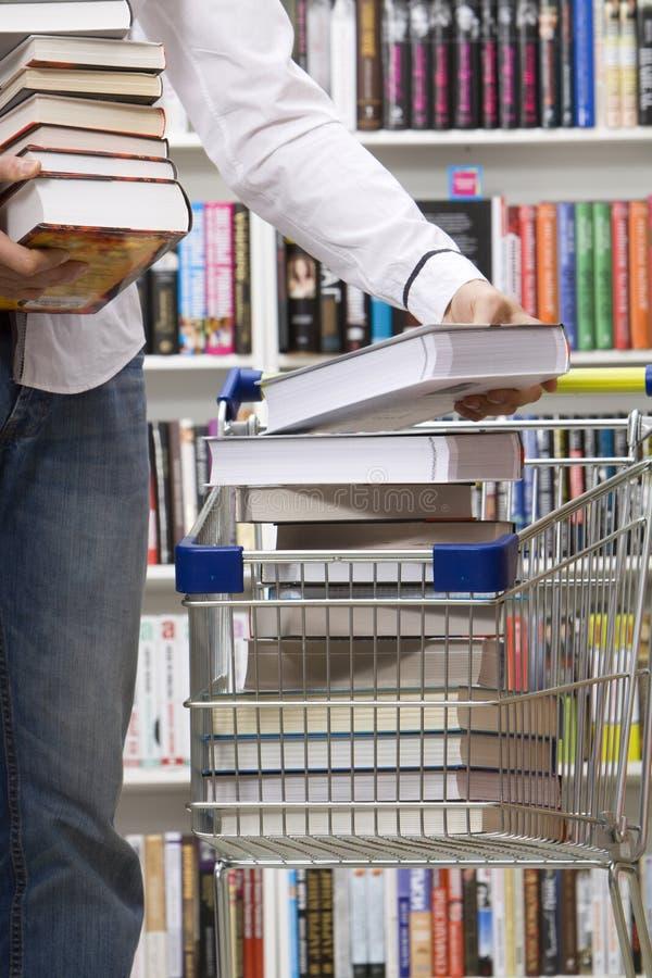 Plan rapproché des mains mettant des livres dans un panier photographie stock