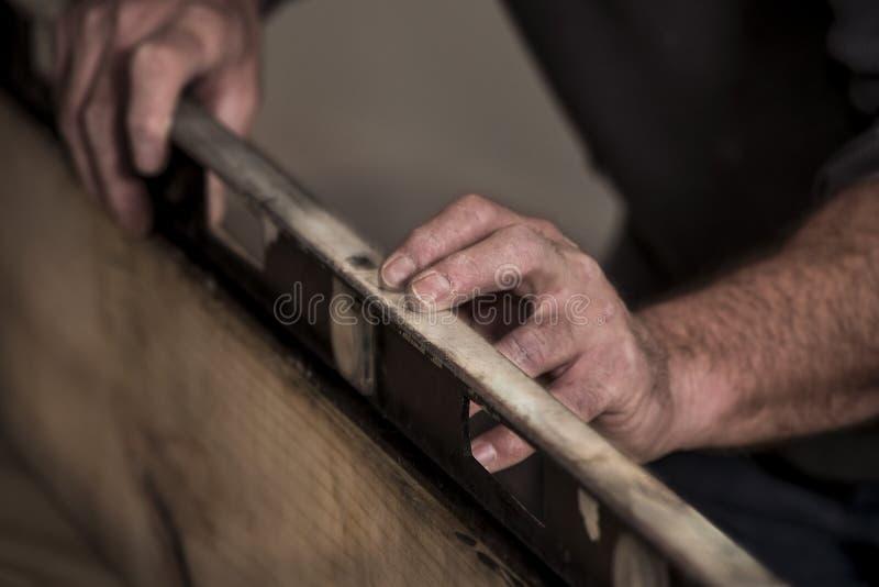 Plan rapproché des mains rocailleuses approximatives du ` s de charpentier utilisant le vieil outil de niveau sur le bord du cons image stock