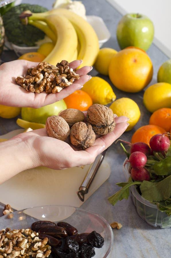 Plan rapproché des mains tenant les noix, fruits à l'arrière-plan photo stock