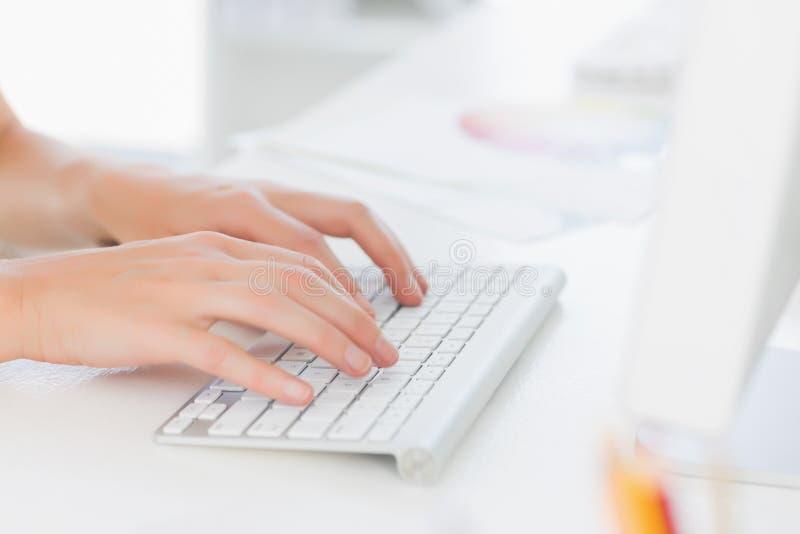 Plan rapproché des mains utilisant le clavier d'ordinateur dans le bureau photos stock