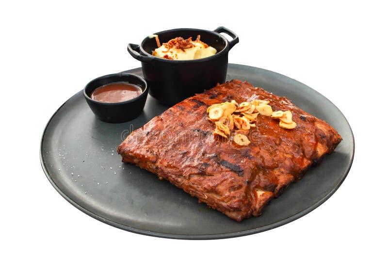 Plan rapproché des nervures de porc grillées avec de la sauce à BBQ d'isolement sur le fond blanc image stock