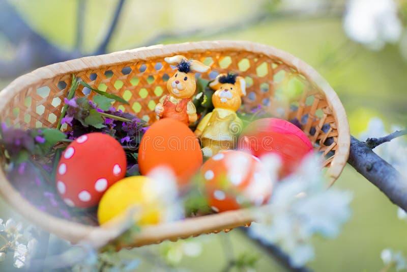 Plan rapproché des oeufs de pâques fabriqués à la main colorés et des petites figurines de lapins dans un panier dehors photographie stock libre de droits