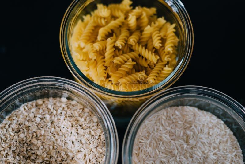 Plan rapproché des pâtes, du riz, et de la céréale de macaronis dans des bols en verre sur un fond foncé photo stock