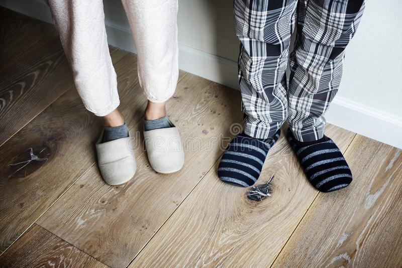 Plan rapproché des pantoufles de port de couples sur le plancher en bois photos libres de droits