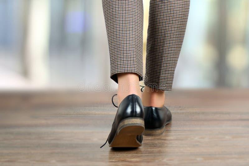 Plan rapproché des pieds de marche de femme dans des chaussures noires sur le plancher images stock