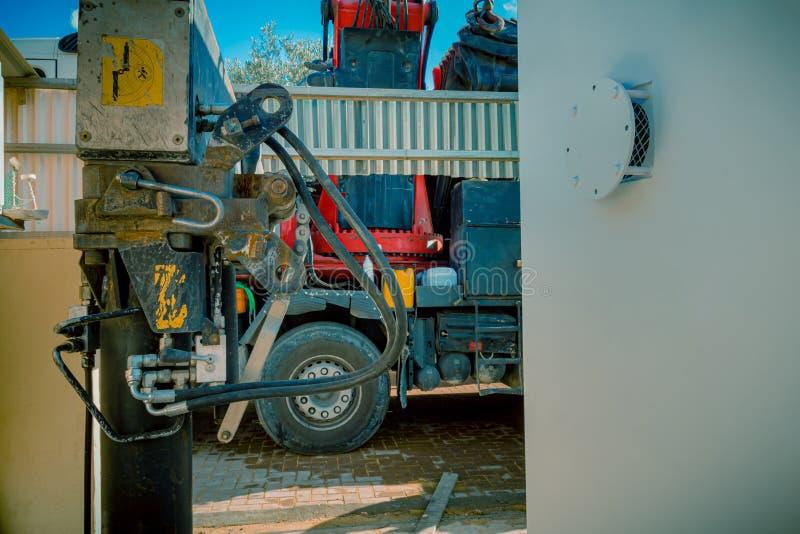 Plan rapproché des pistons hydrauliques d'un camion de calage se garant avec la machine de levage lourde de bras de grue images libres de droits