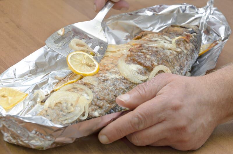 Plan rapproché des poissons rôtis savoureux de carpe dans l'aluminium Chef disposant les poissons rôtis à servir le plat photo libre de droits