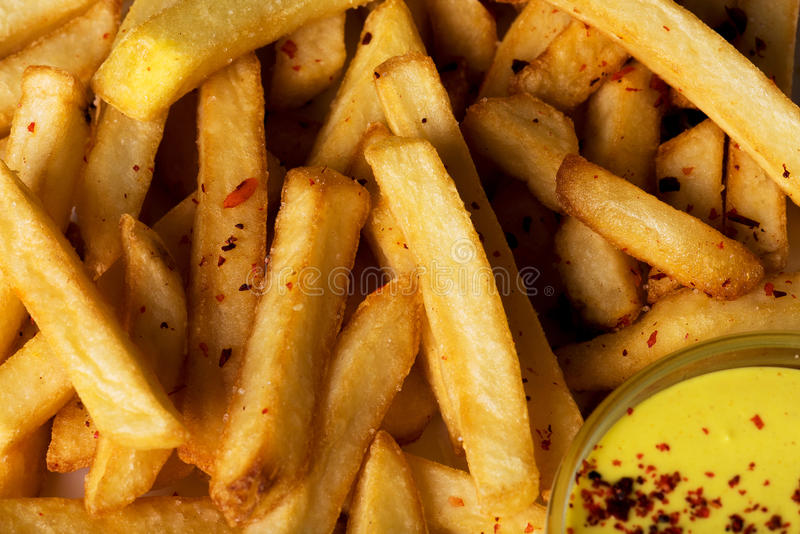 Plan rapproché des pommes frites avec de la sauce au fromage et des épices photographie stock libre de droits
