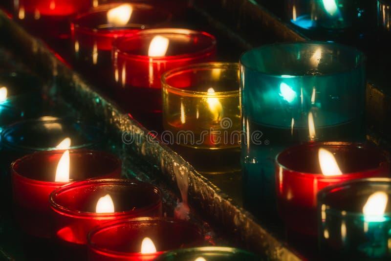 Plan rapproché des rangées des bougies brûlant dans les tealights en verre multicolores à un foyer sélectif d'église photos libres de droits