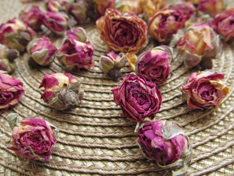 Plan rapproché des roses sèches sur le fond en osier de couverture photographie stock libre de droits