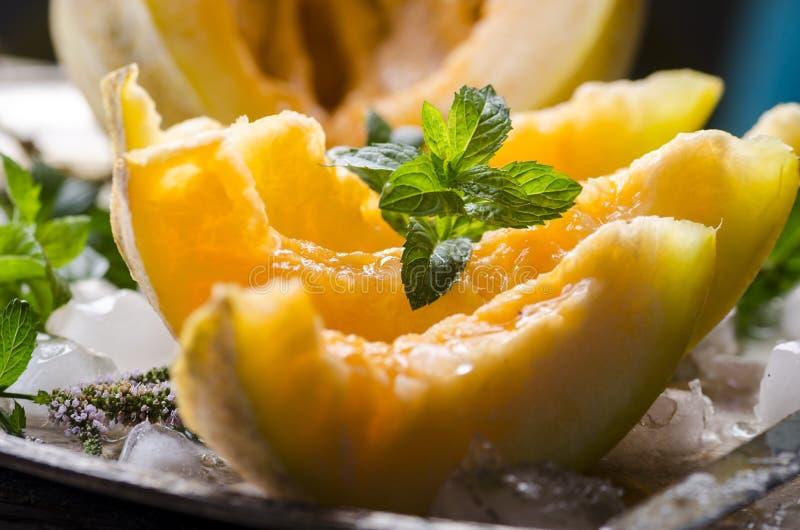 Plan rapproché des tranches de melon de cantaloup avec la menthe et la glace servies du plat de ruban de cru images libres de droits