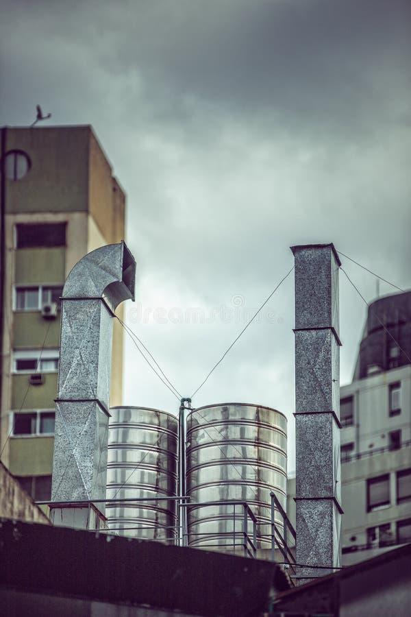 Plan rapproché des tubes et des tuyaux sur un bâtiment avec un ciel gris nuageux à l'arrière-plan photo libre de droits