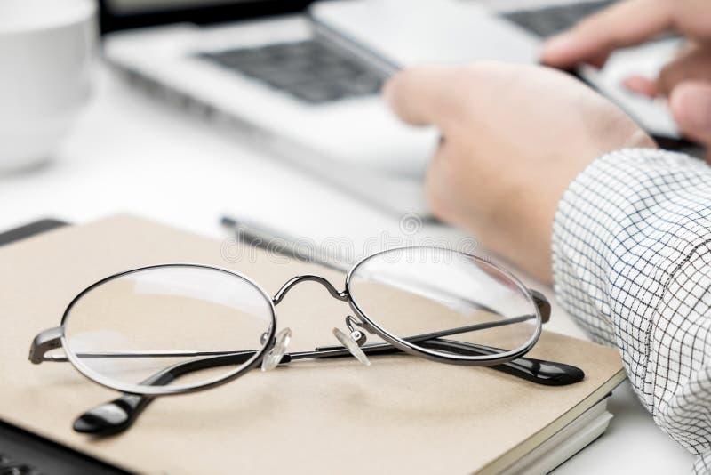Plan rapproché des verres d'oeil avec un homme d'affaires utilisant son smartphone à l'arrière-plan derrière photos stock