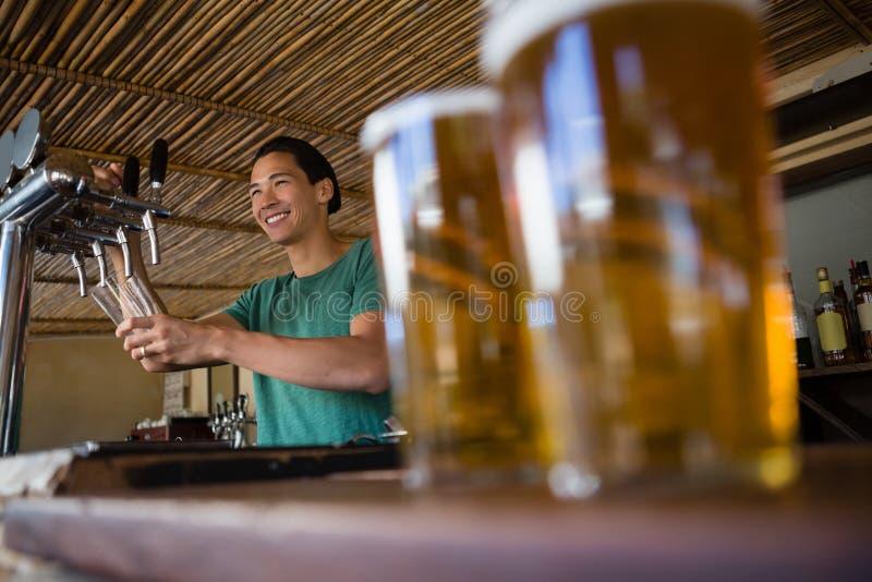 Plan rapproché des verres de bière avec le barman regardant loin photo libre de droits