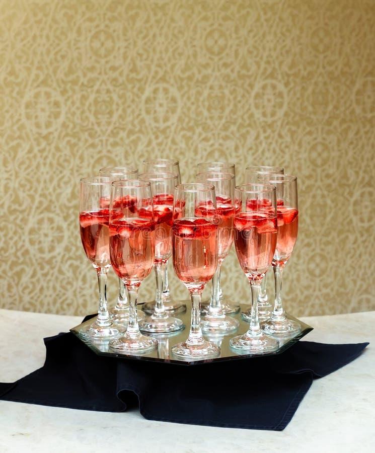 Plan rapproché des verres de champagne dans une rangée sur un champagne de portion de champagne de table sur un plateau photographie stock