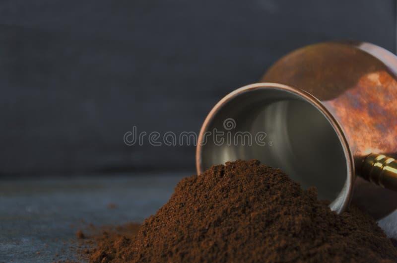 Plan rapproché du cafè moulu contre le pot de café et le mur foncé photographie stock libre de droits
