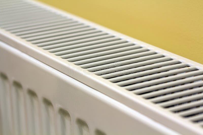 Plan rapproché du détail de chauffage blanc de radiateur sur le fond jaune-clair de l'espace de copie de mur Intérieur à la maiso images stock