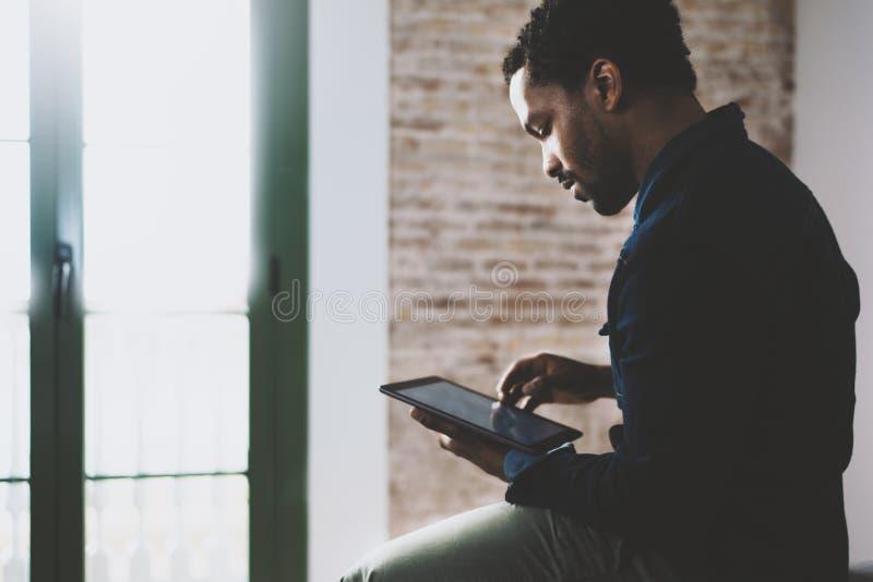Plan rapproché du jeune homme africain barbu à l'aide de l'ordinateur portable tout en se reposant sur le sofa à son siège social photo stock