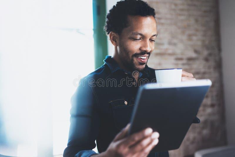 Plan rapproché du jeune homme africain barbu à l'aide du comprimé tout en jugeant le café blanc de tasse disponible au bureau cow images stock