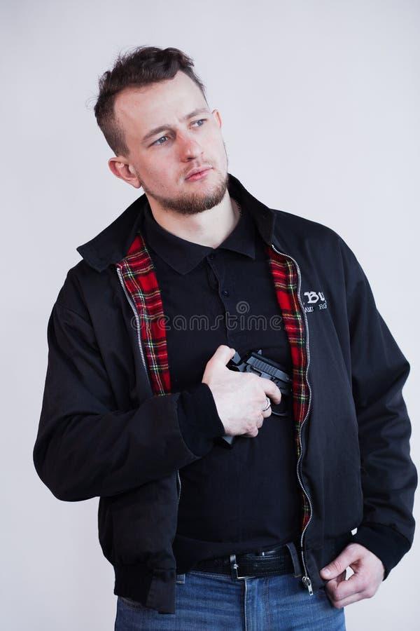 Plan rapproché du jeune homme focalisé se tenant et visant avec l'arme à feu photographie stock