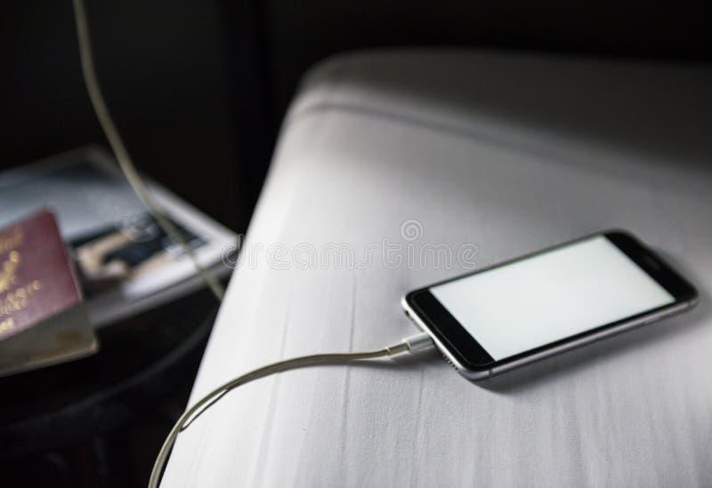 Plan rapproché du mensonge de remplissage de téléphone portable mort sur le dos blanc de tissu photo stock