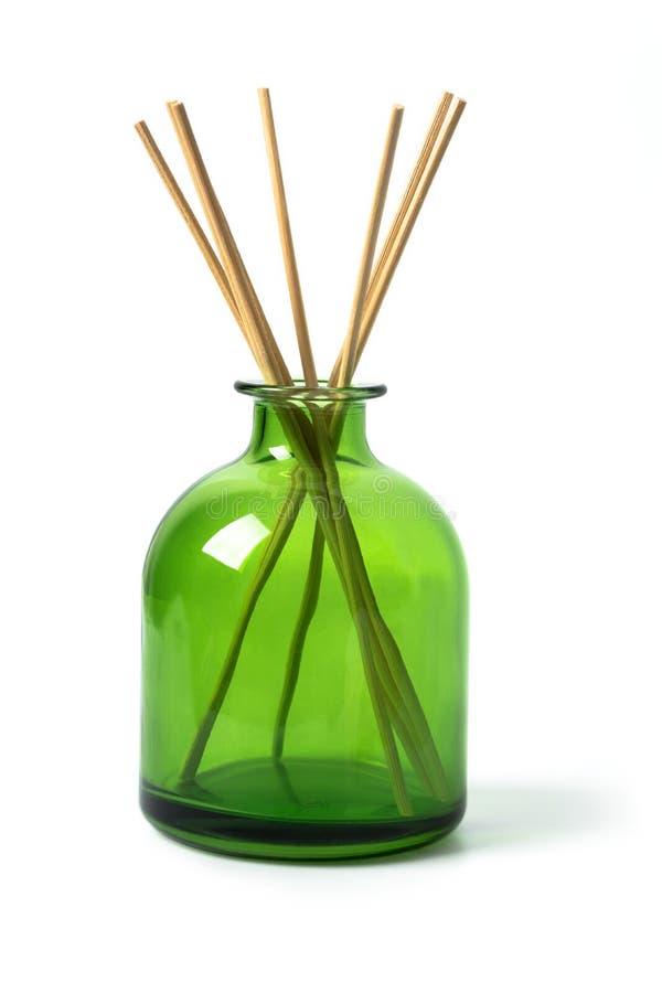 Plan rapproché du parfum à la maison dans une bouteille en verre verte sur le dos blanc photographie stock libre de droits
