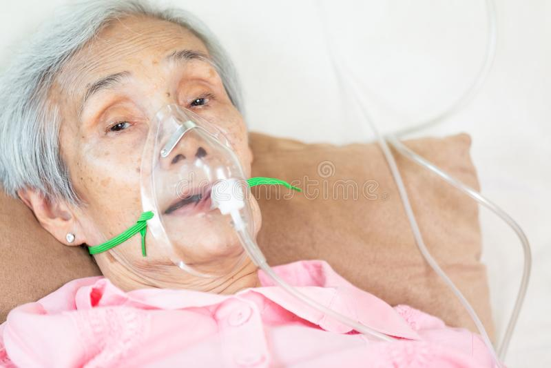 Plan rapproché du patient supérieur féminin mettant le masque à inhalation ou à oxygène dans le lit d'hôpital ou la maison, subir photographie stock