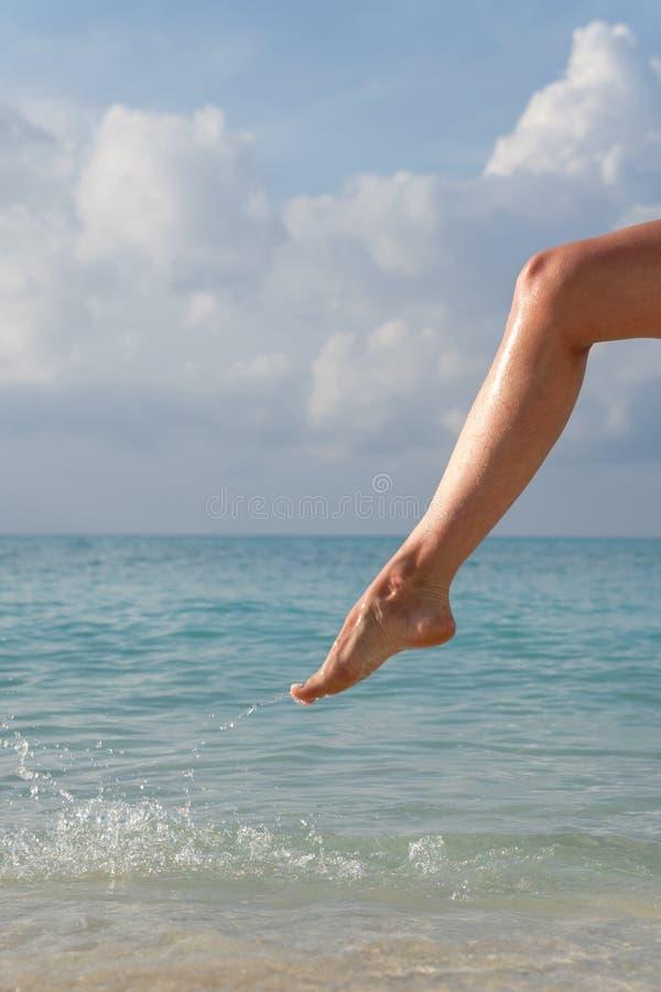Plan rapproché du pied de la femme sur quels écoulements d'eau de mer images stock