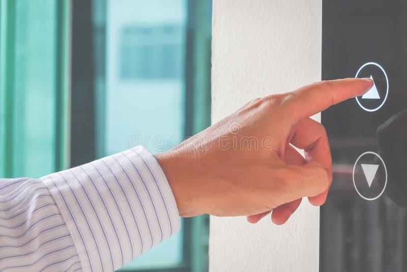 Plan rapproché du pressing du doigt d'un homme sur le bouton ouvert d'ascenseur photos libres de droits