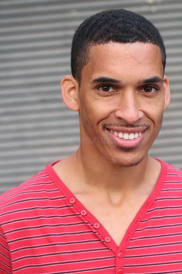 Plan rapproché du sourire jeune, homme à la peau foncée photographie stock