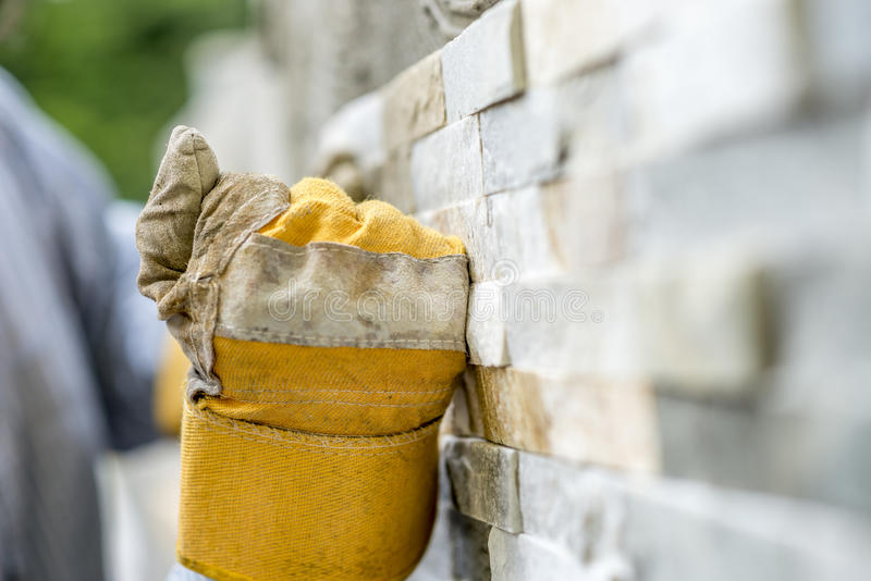 Plan rapproché du travailleur manuel dans des gants de protection couvrant de tuiles un esprit de mur image stock