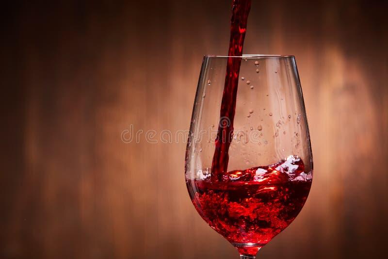 Plan rapproché du vin rouge savoureux versant dans le verre à vin fragile pur se tenant sur le fond en bois photos libres de droits