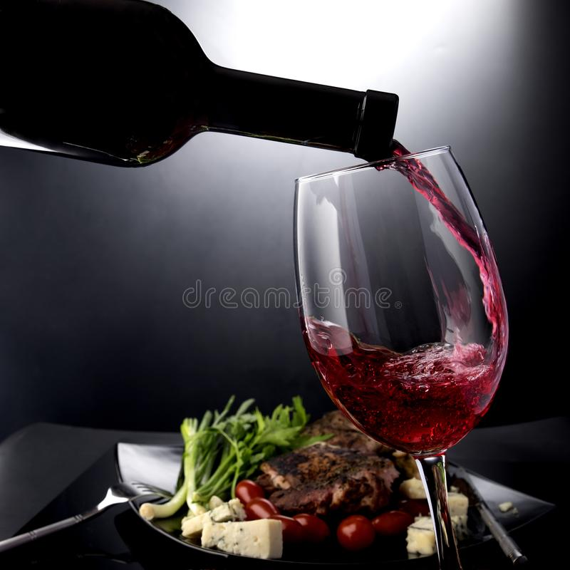 Plan rapproché du vin rouge versant dans un verre avec du fromage et la viande photo stock