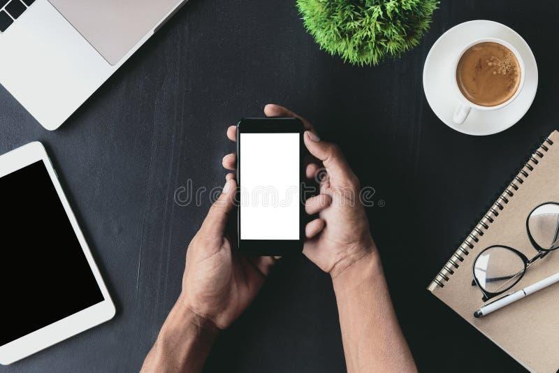 Plan rapproché en main tenant le téléphone montrant l'écran blanc sur le bureau photos stock