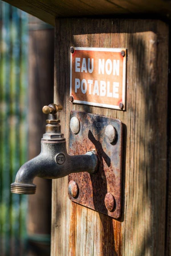 Plan rapproché ensoleillé de robinet rouillé avec de l'eau d'avertissement non potable images stock