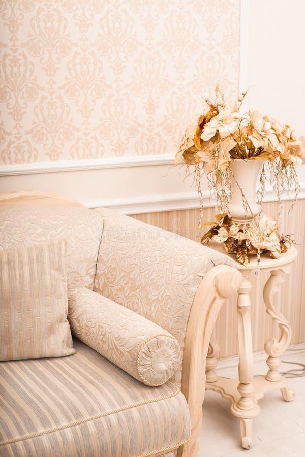 Plan rapproché et vase classiques blancs de sofa avec les branches d'or et image libre de droits
