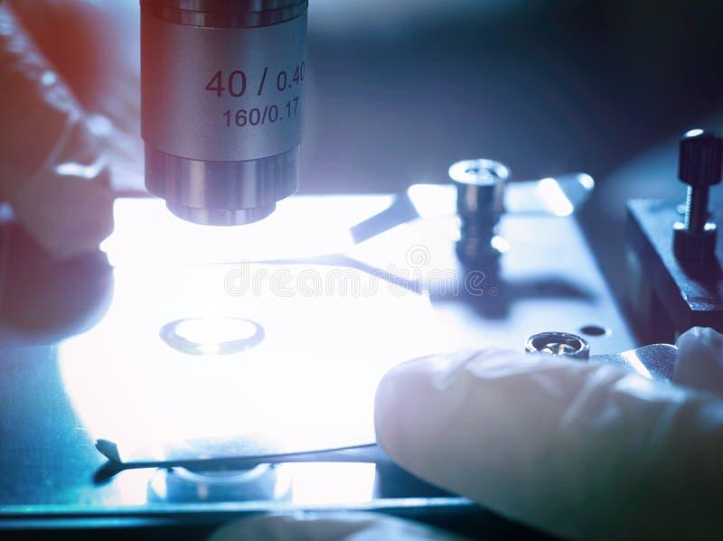 Plan rapproché examinant un échantillon de liquide sur un microscope photos libres de droits