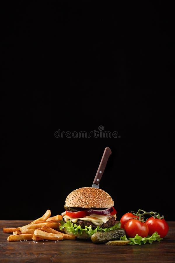 Plan rapproché fait maison d'hamburger avec du boeuf, la tomate, la laitue, le fromage, l'oignon et les pommes frites sur la tabl photos stock