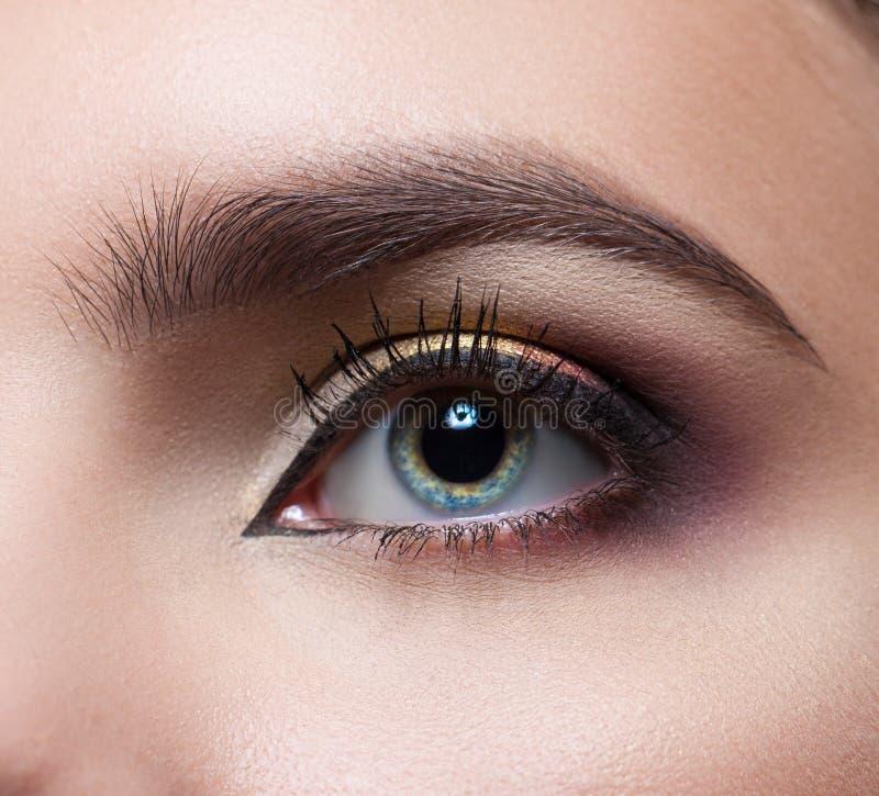 Plan rapproché femelle d'oeil Maquillage parfait et sourcils Beaux yeux gris photographie stock