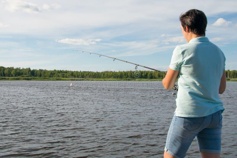 Plan rapproché, femme sur le fond d'un beau lac et ciel bleu, pêchant avec une canne à pêche, vue arrière photos libres de droits