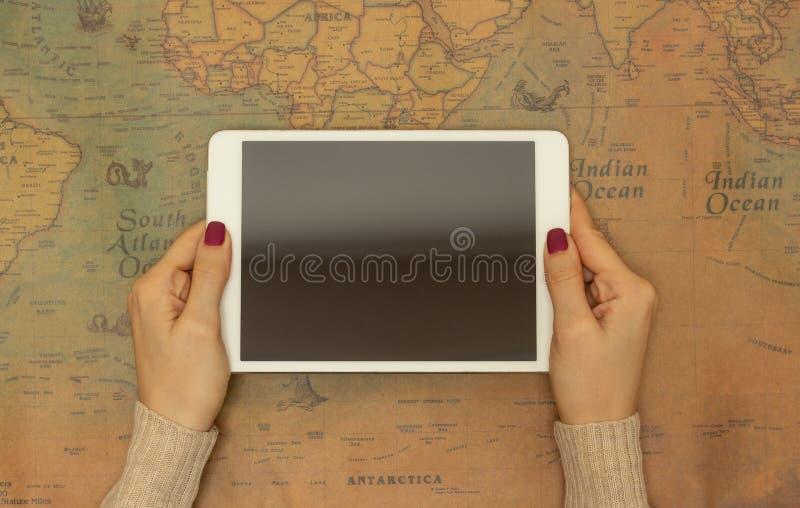 Plan rapproché, fille tenant un comprimé sur le fond d'une carte du monde, le concept de trouver un pays pour le voyage photographie stock