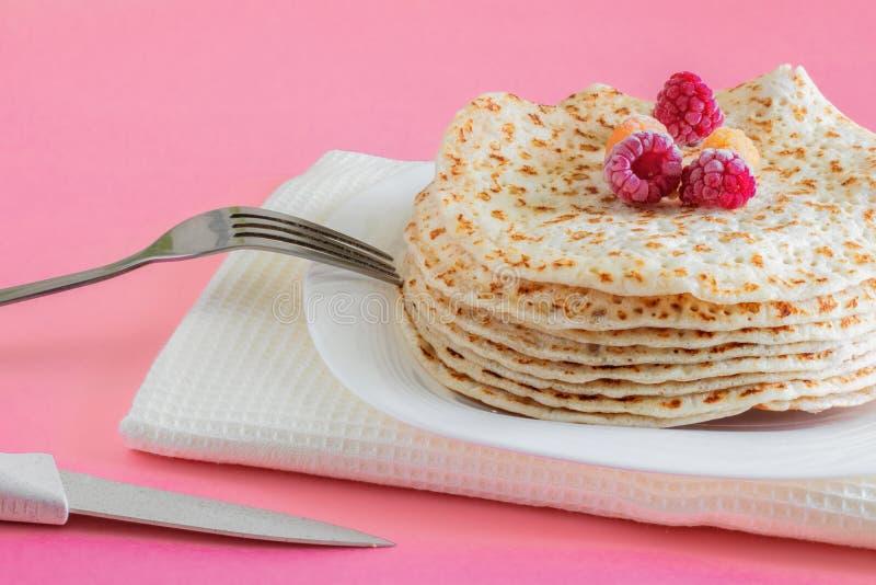 Plan rapproché frit de crêpes d'un plat blanc, crêpes avec les framboises, dessert sur un fond rose, endroit pour le texte images stock