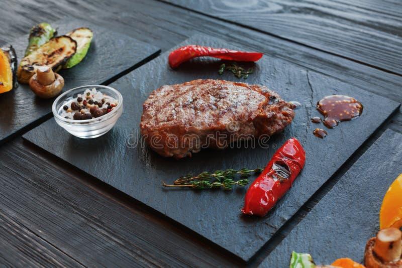 Plan rapproché grillé de bifteck de boeuf sur le fond en bois foncé de table images stock